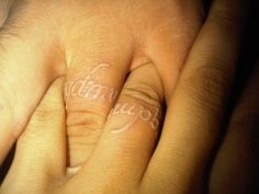 Matching white ink ring finger tattoos, Que Quieres De Mi Vida (what do you want from my life)
