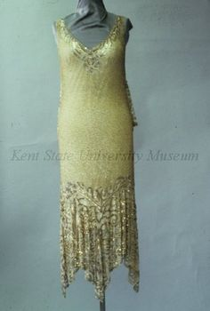 1920s, Gold beaded and sequined evening dress. Dress with sequins at neck in scrolls and flowers, free back center panel with embroidered scrolls of sequins and bugle beads, body with gold beads, the bottom with pointed dipping hem embroidered with scrolls of sequins. Front view