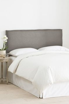 Love the gray with the white sheets.  Cute wood night stand too.  French Seam Slipcover Headboard - Linen Grey