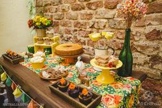 Geral da mesa de festa junina: passadeira de chita, pequenos cupcakes, doces típicos e garrafa para decorar.