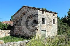 Abandoned stone Mediterranean house surrounded with overgrowth and stone walls