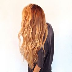 Long healthy blonde hair with a soft beach wave.