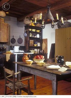KITCHENS - Early American Primitive look to a new home. Flea market finds, weathered pieces, yellow ware baskets, pierced tin light fixture, exposed beam ceiling, farm table with baking supplies for apple crisp or pie, antiques, nostalgic [LJW1_2713-003]