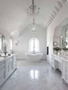 Stunning bathroom features a barrel ceiling lined with a crystal droplets chandelier suspended over a freestanding curved bathtub placed under an arched window framed by white and gray marble tiles placed next to a recessed fireplace.