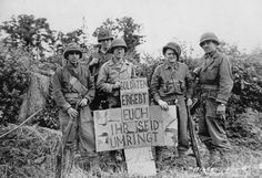 "The soldiers of the American patrol pose with a warning in German, in the French city of Saint-Lô: ""Soldaten, ergebt Euch. Ihr seid umringt"" - ""Soldiers, surrender, you are surrounded.""  Source: ""GeoEpoche Panorama, Zweiter Weltkrieg."" Nr. 6 - 2015."
