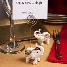 """Each measures 4"""" tall x 2"""" wide A silver metal wire extends up to form a coiled holder for easy insertion of a place card, photo or note A great choice as traditional Indian wedding favors and as good luck favors for all occasions Bulk packed with a blank place card included."""