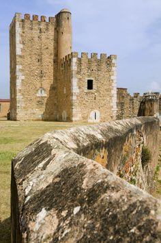 Este edificio alto, viejo, marrón y blanco se llama la fortaleza de Ozama es en Santo Domingo, República Dominicana.