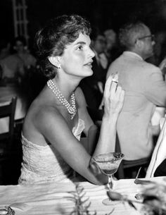JACKIE BOUVIER KENNEDY practiced yoga but she also smoked. Here she is photographed in July 1954 having dinner with the Spanish ambassador at the Shoreham Hotel in Washington.