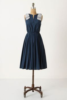 Dizzyingly romantic, this blue-grey cotton frock tumbles into waist pleats below a bow-topped V-neck bodice. By Portrait of a Girl.