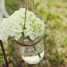 Shepherd's hooks lined the aisle with hanging jars filled with white and green blooms.