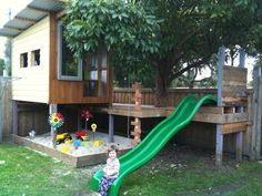 deck and playhouse with slide and sandbox