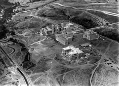 (1929)* - Aerial view of the UCLA campus during construction. View shows Royce Hall, left rear, and the Physics building, center right. Both buildings were built in 1928-29, and designed by Allison and Allison, Architects. Haines Hall, right rear, was built in 1928. Powell Library, center left, was built in 1927-29. Moore Hall (under construction), in foreground, was built in 1930. These three buildings were designed by architect George W. Kelham. All five campus buildings were constructed…