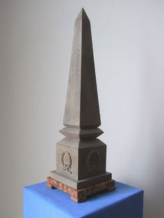 "A Patinated Grey Wood Obelisk ; the base decorated on all four sides with ""victory wreaths"" ; the base resting on a marble plinth - Dim: H: 53.5 cm (with base), W: 14.5 cm, D: 14.5 cm - Weight: 2.4 kg."