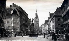 Kaiserstrasse Freiburg mit Bertoldsbrunnen und Martinstor    Schöne Sicht durch die Kaiserstrasse Freiburg in Richtung Süden. Mit Bertoldsbrunnen, Löwen-Apotheke und Martinstor. Aufnahmedatum vermutlich in den 1920er oder 1930er Jahren.  Die Historie der