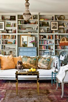 Library - New Orleans Cottage Revival - Southernliving. The homeowners scoured the city for key architectural components, vintage furniture, and accessories, like this pale blue Swedish chest that sits in a niche in the bookshelves.