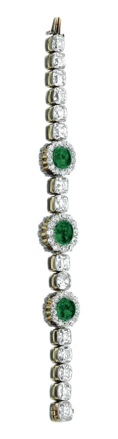EMERALD AND DIAMOND BRACELET, 1900S. Composed of a line of old mine diamonds, interspersed with three clusters each centring on a cabochon emerald within a surround of circular-cut diamonds, length approximately 170mm.
