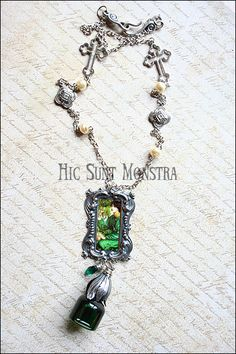"""""""L'Absinthe Fou"""" - a celebration of the green fairy nectar and of Dante Gabriel Rossetti's art, assembling with elegance a lovely bottle with a flower cap, and a long chain enriched by beautiful connectors, crystals and glass pearls.  https://www.facebook.com/hicsuntmonstra/"""
