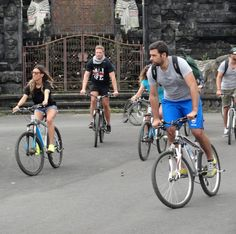 Tourists biking in front of a temple in Bali, Indonesia
