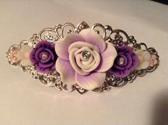 80mm silver filigree barrette with a faded 25mm light purple clay rose and smaller purple and pink polymer flowers centered with clear gems. $15