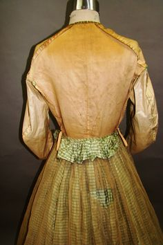 """Light green & cream checked taffeta 1860's. Green silk trim cut in scallops, gathered on string, hand stitched to dress. 9 silk & tatted ball buttons. Skirt lined with tarlatan, bottom faced w/green braid & polished cotton. Coat sleeves look like pagoda sleeves. Bodice flat lined w/muslin. Pocket. Separate belt lined w/polished cotton, closes at front w/overlap & belt loop. Center bow in back. Waist & armscyes piped. Waist 22"""", bust 30, skirt front 41, back 47, circ 140"""", Back neck-waist 15."""