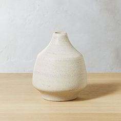 Shop Lunar Ivory Vase.   Hand-casted from stoneware, large bud vase is finished with ivory reactive glaze then fired at higher-than-usual temps to create a unique textured surface.  Watertight to hold your favorite blooms.  Striking solo, too.