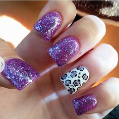 Purple sparkly nails with a white accent nail with sparkly purple and black cheetah print design on them on fake acrylic nails with shellac polish