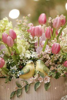 Arranjo com tulipas, orquídeas e outras flores em tons de rosa com folhagem pela Milplantas em cachepot maravilhoso da Vestindo a Mesa, feito à mão pela Zanatta Casa! Este foi apenas um detalhe desta mesa de jantar!