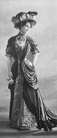 """Wow and wow!  Circa 1907 photo of a lovely lady opulently adorned in a """"visiting dress"""" with fabrics, tassels, beading, embroidery, as well as  and bows upon the magnificent hat. Original text in French:   Robe de visite par Redfern, 1907."""