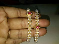 Pearl Bangles: Two Pearl Bangles studded with Rubies in between.