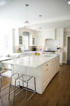 1936 Colonial LEED RemodelWhite and Aqua Kitchen White inset cabinets are highlighted by White Princess quartzite countertops and aqua blue accents.  Maybe darker marble?