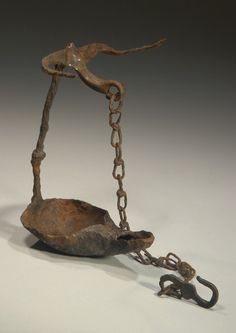 DANUBIAN CELTIC HAMMERED IRON BOAT-SHAPED HANGING OIL LAMP.   Hanging shaft with knot decoration with horns and curved end with original chain and S-shaped hook. 2nd-1st Century BC  H. without chain 6 7/8 in. (17.5 cm.)  Ex German collection  Published: J. Eisenberg, Art of the Ancient World, 2010, no. 179.  HMQ38  $6,500