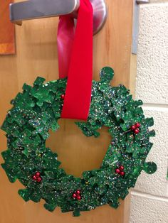 Grade one puzzle wreath.  Tip: use three sizes of puzzle pieces.   Ask families to donate old puzzles for class art.