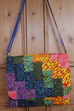 This large patchwork messenger style bag is made from a selection of batik fabrics in colours of the rainbow. Each bag I make is unique due to a different selection of fabrics being used, and these rainbow bags are made to order.