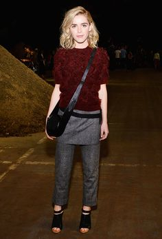 Kiernan Shipka wears a burgundy top with gray trousers, a crossbody bag, and sandals