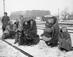 The only survivors of 150 Polish people who walked from Lodz, Poland to Berlin Huddle in blankets, on December 14, 1945. They are waiting by a railway track hoping to be picked up by a British army train and given help.