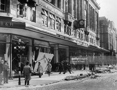 Shop assistants assist ARP staff to clear debris from damaged windows at Bourne & Hollingsworth's department store in London's West End after a German bombing raid, 18th September 1940.