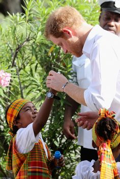 He's a big kid at heart: Prince Harry helped out a smiling child blow bubbles...