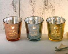 Metallic Message Tea Light Holders.   Set of 3 metallic glass tealight holders in gold, silver and copper. Each comes with a different motivational message. Size of each H7.5 x D7.5cm. Tealights not included. Please see page 30 for tealights.