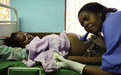 Nurse Melifa Mphasa listens to the pregnant belly of her patient in the labor ward at Bwalia 'Bottom' Hospital in Lilongwe, Malawi.