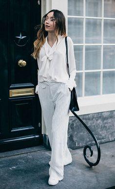 Street style look com camisa laço e calça listrada