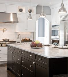 This dark espresso island is stunning.  Subway tile w/matching grout & bright white cabinets make this kitchen is very crisp & clean looking