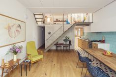 Metal stair in a renovated row house combines the living room and kitchen with colorful details.