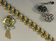 Group of Schiaparelli Jewelry Comprising a dangling pine cone pin with iridescent rhinestones, Victorian design pin with blue faceted stones and drop tassel, and gilt-metal link necklace with faux cabochon emeralds.
