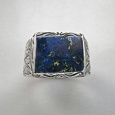 A full engraved sterling silver men's signer ring. It has a plain curved rectangle Lapis Lazuli natural gemstone on top, which is decorated, all around with hand engraving. On both sides of this beautiful mens ring there are two crosses with floral decoration. A jewelry piece,