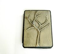 A Kindle case cover with a modern pewter repousse tree with a flowing detail in the background.