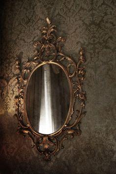 ornate mirror on taupe tone on tone wallpaper