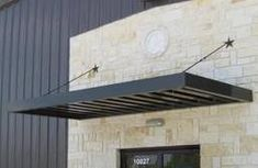 This industrial steel awning is modern yet refined. Great for restaurants and businesses, and even a modern home. Accents the white marble facade. Metal Door Awning, Front Door Awning, Window Awnings, Fabric Awning, Door Canopy, Marquise, Pink Houses, Entry Doors, Windows And Doors