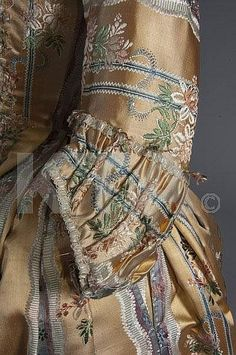 A brocaded apricot robe à la française, circa 1765-70, woven with blue and mauve stripes and undulating flowerheads, the upper bodice lined in linen with internal lacing, saque-back, with compères formed of horizontal tabs, front robings trimmed in fly-braid, matching petticoat,