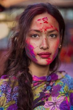 She's Sona during Holi, the festival of colours. This huge Hindu celebration is one of the most spectacular in the world. The day when spring comes, when good triumphs over evil, a moment to forgive and to be forgiven. I took this photo on the streets of Kathmandu, Nepal.