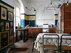 Beautiful blue tile in the kitchen, nice old banged-up floors and original portraits on the left wall. Excellent space.